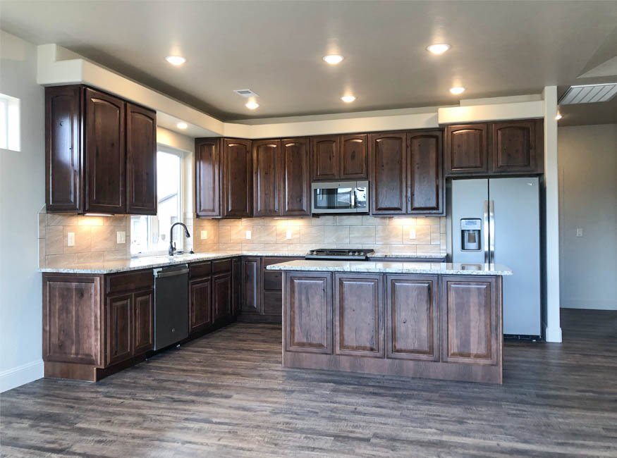 The kitchen of the sapphire model includes all appliances, has a center storage island with a breakfast bar area, and a window over the sink.