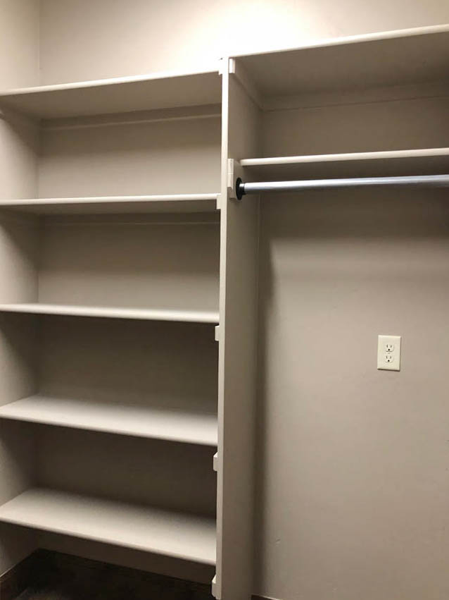 The laundry room in the Ruby model includes open linen shelving behind the door.