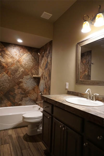 The hall bath of the Ruby model includes a cast iron tub with a shower and custom tile work, a toilet, and vanity.