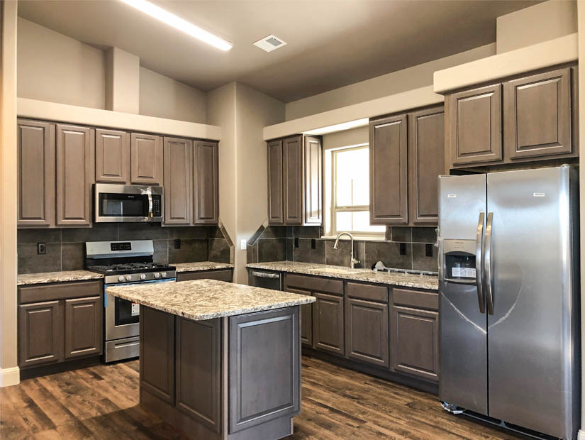 The kitchen in the Ruby model includes a pantry, appliances, and a center island with an eating area.