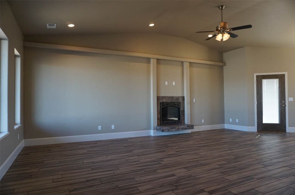 The living room of the Ruby model has vaulted ceilings, a gas fireplace, and large front facing windows overlooking the covered front porch.