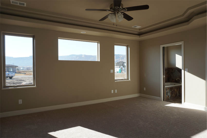 The master suite of the Ruby has window for natural light, a walk-in closet, and access to the covered back patio.