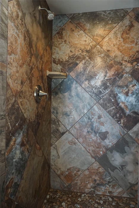 The master shower in the Ruby model has custom tile work and a crushed tile base.