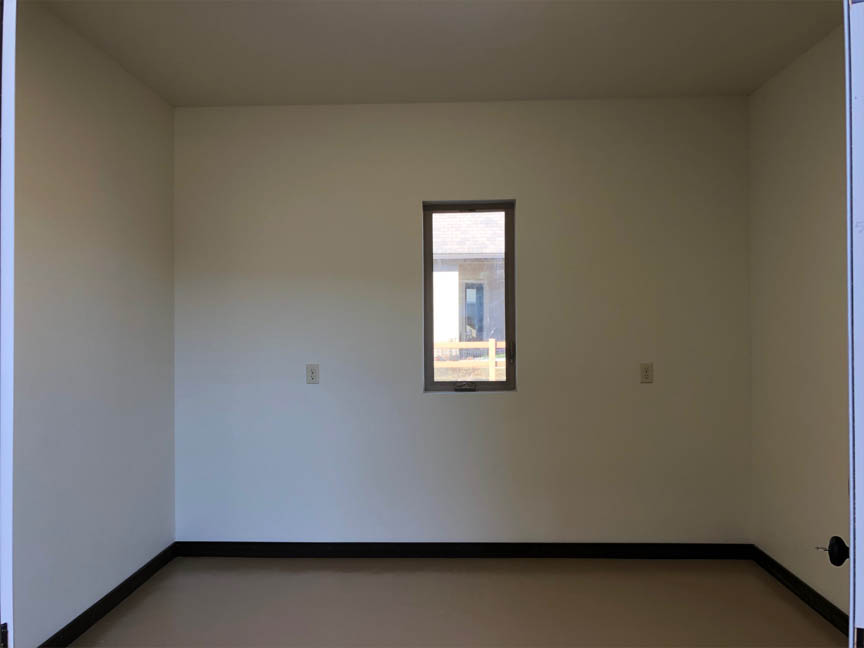 The storage room off of the garage in the Ruby is finished out with sheetrock, paint, and TREX® baseboard.
