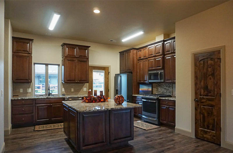 The kitchen of the Topaz model includes a storage island with an eating area, a walk-in pantry, and appliances.