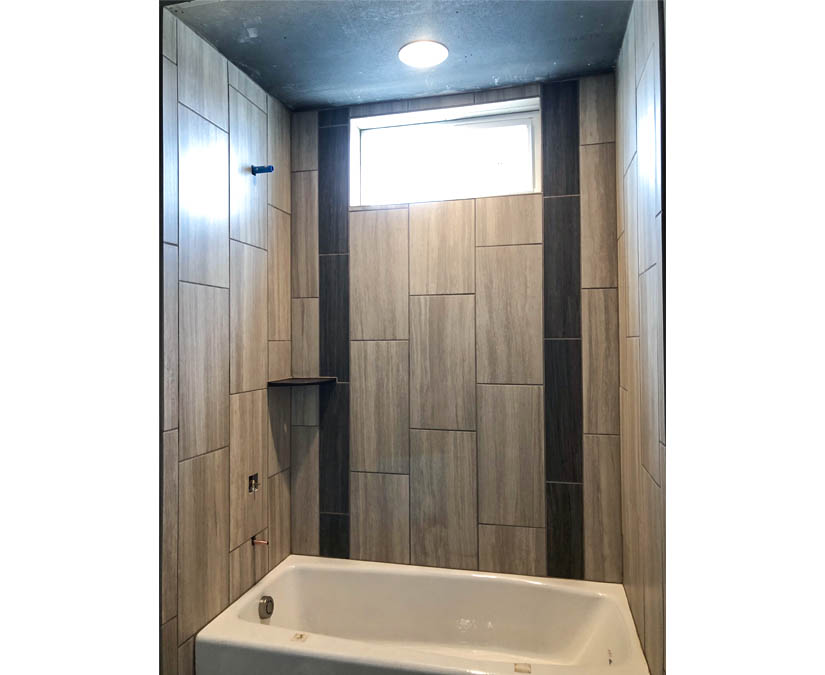 The hall bath of the Topaz model includes an in-tub shower, vanity, toilet, and linen closet.